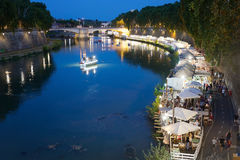 Along the Tiber River in Rome`s summer nightlife. Rome, Italy - July 30, 2017: In the scene the protagonists are the people who stroll down to the river and Royalty Free Stock Photos