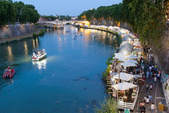 Along the Tiber River in Rome`s summer nightlife. Rome, Italy - July 30, 2017: In the scene the protagonists are the people who stroll down to the river and Stock Images
