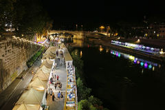 Along the Tiber River in Rome`s summer nightlife. Rome, Italy - July 30, 2017: In the scene the protagonists are the people who stroll down to the river and Stock Image