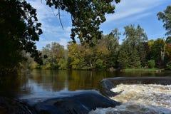 Alonge der Flussrand mit Wasserfall lizenzfreie stockbilder