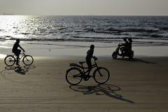 Alongshore het cirkelen en rit op een autoped op het strand stock afbeeldingen