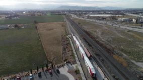 Following Public Transit Train near Rocky Mountains of Salt Lake Valley. Alongside of I-15 along the Wasatch Front of northern Utah are the rail tracks that stock footage
