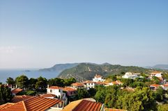 Alonissos island with red roofs, green trees, hills and the sea. Royalty Free Stock Photography