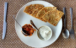 Aloo Paratha with pickle and curd. Served on while plate , and photographed with Knife and fork , photographed against mat Stock Image