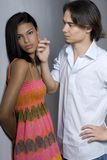 Aloof. A young woman looks away from her boyfriend who is trying to make up stock images