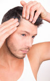 Alopecia male. Male checking hair for alopecia in mirror Stock Image