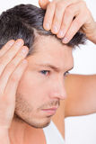 Alopecia male. Male checking hair for alopecia in mirror Royalty Free Stock Photography