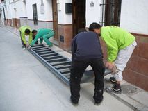 Taking delivery of steel staircase. Alora, Spain - December 15, 2011: Men preparing to lift steel staircase outside village house in Andalusia Royalty Free Stock Photography