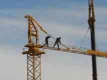 Men erecting large yellow crane Royalty Free Stock Images