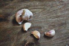Aloves crudi dell'aglio sul tagliere Immagini Stock