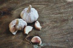 Aloves crudi dell'aglio sul tagliere Fotografia Stock