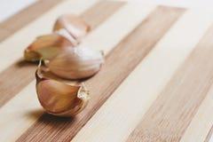 Aloves crudi dell'aglio sul tagliere Fotografie Stock Libere da Diritti
