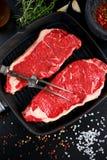 Aloyau cru de bifteck de boeuf de viande fraîche pour deux en fer casserole grillée avec des herbes image stock