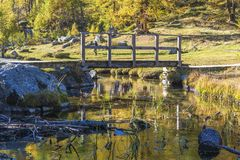Alpe devero autumnal mountain landscape. A slowly flowing river with a small wood bridge inside the Alpe Devero flat land royalty free stock photo