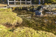 Alpe devero autumnal mountain landscape. A slowly flowing river with a small wood bridge inside the Alpe Devero flat land royalty free stock images
