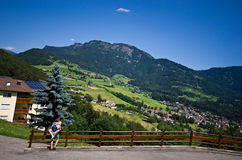 Alpe di Siusi in summer. A happy couple of tourists embracing on a fence with scenic view of Italian town of Alpe di Siusi, Bolzano region, Dolomites Stock Image