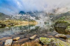 Alpejski jezioro z odbiciami chmury i niebo Fotografia Stock