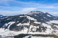 Alpejski zima krajobrazu szczyt z śniegiem, lasem i chmurami, zdjęcie stock