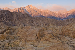 Alpen Glow Eastern Sierra. Alpen glow on Eastern Sierra Mountains with the Alabama Hills in the foreground, California, USA Stock Photo