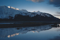 Alpenglow on Alaska Mountains. A calm, peaceful morning at dawn on the Chilkat Inlet in Haines Alaska. The distance reveals the Chilkat Range reflecting Royalty Free Stock Photo