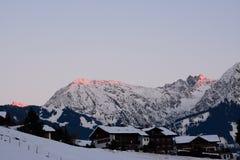 Alpenglow på dolda berg för snö Royaltyfri Foto