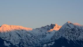 Alpenglow on snow covered mountains Stock Photo