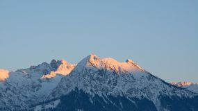 Alpenglow on snow covered mountains Royalty Free Stock Photos