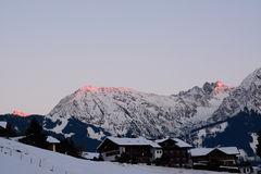 Alpenglow on snow covered mountains Royalty Free Stock Photo