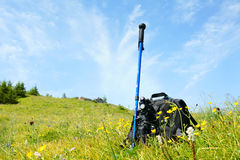 Alpenstock and backpack. A blue alpenstock and a black backpack lie on grass,under the sky Royalty Free Stock Photos