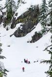 Alpental WA - 2/7/16 :滑雪者挡雪板滑雪巡逻在峭壁下的山抢救 免版税库存照片