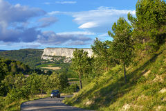 Alpes de Haute Provence. PROVENCE, FRANCE - JUL 10, 2014: Car on the rural road in Alpes de Haute Provence, a part of the annual Tour de France route. Sunset Royalty Free Stock Images