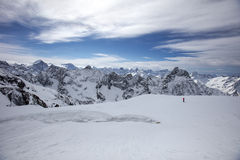 A man takes a photo of a winter landscape in the alps. Royalty Free Stock Photo