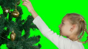Alpha channel transparent background. Close up portrait. Young white blonde caucasian girl decorate christmas tree with. Golden ball. Young girl hanging to stock footage