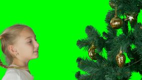 Alpha channel transparent background. Excited young white girl decorating christmas tree and with happy looking to. Firtree. Close up portrate of blonde white stock video footage