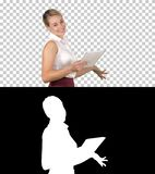 Female office clerk walking with tablet and smiling broadly when talking to camera, Alpha Channel royalty free stock photography