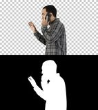 Side portrait of a happy student walking and talking on mobile phone, Alpha Channel royalty free stock image