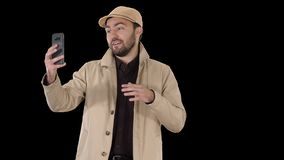 Young man making a video call from his mobile phone while walking, Alpha Channel stock footage