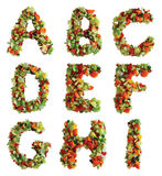 Alphabet. Letters of the alphabet A through I made from lettuce, tomato, carrot, yellow pepper and cucumber. Isolated on a white background royalty free stock photography