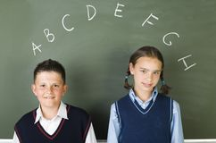 Alphabet. Young, smiling boy and girl, standing in front of blackbopard. Looking at camera, front view Stock Photos