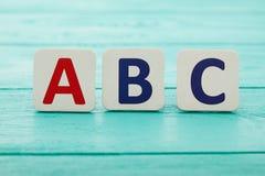 Alphabet abc on blue wooden table background. Copy space. ABC education concept. Selective focus stock photo