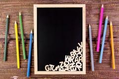 Alphabet anglais en bois sur le tableau noir Crayon de couleur sur en bois Photographie stock libre de droits