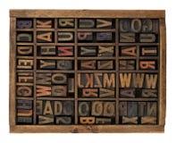 Alphabet in antique wood letterpress types. Vintage wood letterpress types, stained by ink, placed randomly in typesetter drawer, isolated on white Stock Photo