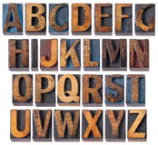 Alphabet in antique wood type. Complete English alphabet - collage of 26 isolated vintage wood letterpress printing blocks, scratched and stained by blue, red Stock Images