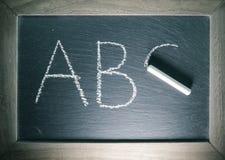 Alphabet beschriftet ABC, das auf Tafel zurück zu Schulkonzept mit Holzrahmen geschrieben wird lizenzfreie stockbilder