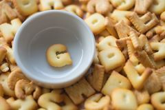 Alphabet biscuit in ceramic cups letters G. Alphabet biscuit in ceramic cups Closeup letters G, random letters Royalty Free Stock Photography