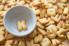Alphabet biscuit in ceramic cups letters K. Alphabet biscuit in ceramic cups Closeup letters K, random letters Stock Photography