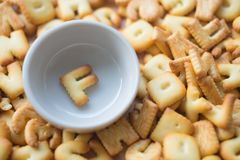 Alphabet biscuit in ceramic cups letters F. Alphabet biscuit in ceramic cups Closeup letters F, random letters Stock Photography