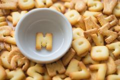 Alphabet biscuit in ceramic cups letters M. Alphabet biscuit in ceramic cups Closeup letters M, random letters Stock Image