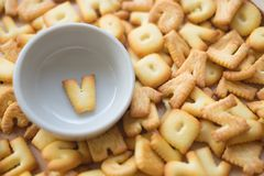 Alphabet biscuit in ceramic cups letters V. Alphabet biscuit in ceramic cups Closeup letters V, random letters Stock Image