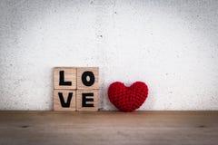 Alphabet-Blöcke und rotes Herz-geformte Seide Stockfotografie